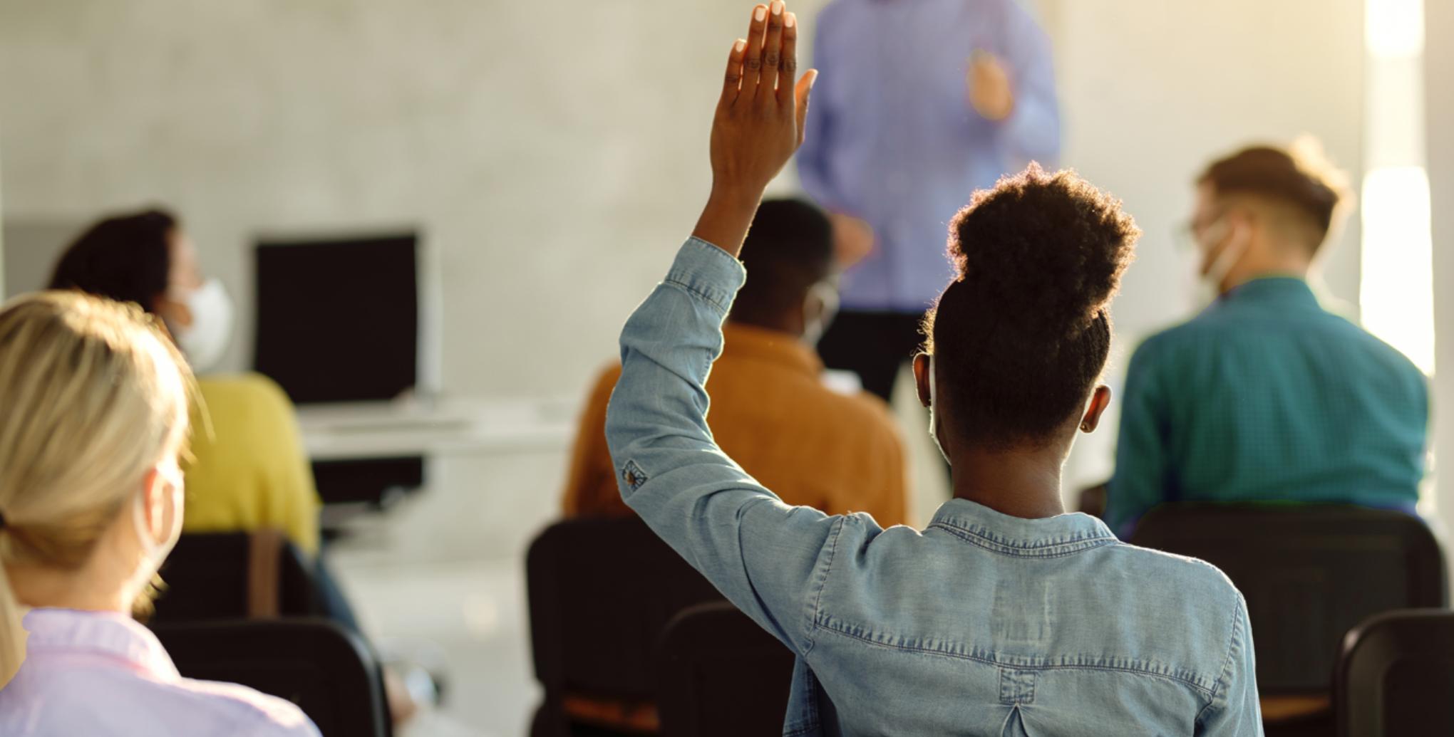 Person raising hand in classroom.