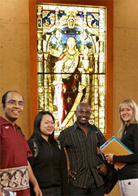 Group photo of students standing in front of stained-glass window