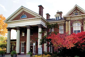 Flavelle House—a decorative brick building with white accents. Four white columns lead to the main entrance. Deciduous trees and shrubs are in view.