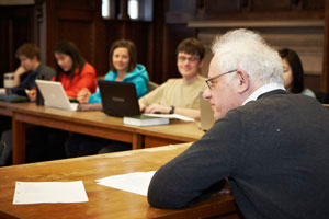 A professor and students are seated at an angled wooden table. Sheets of paper are scattered in front of the professor, who is looking off to his left. Laptops are open in front of the students. Several students look at their laptops, several toward the professor.