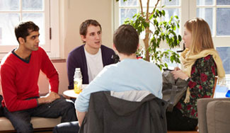 In a well-lit study area, four students sit in a circle of chairs and speak. A potted tree stands behind the students.