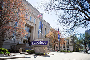 Angled view of the Law School exterior. An American flag flies in front of the main entrance. Many deciduous trees are in view; some are bare, some covered in orange leaves.