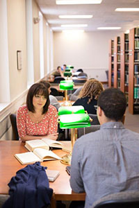 In the library, a female student listens as the male student sitting across from her speaks. Two books are opened in front of her. Other students occupy the row of study tables behind her. Two green desk lamps sit on each table.
