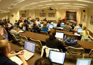 Law students sit with open laptops, listening to their professor give a lecture.