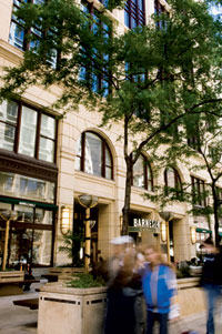 Blurred people walk past an urban Barnes & Noble retailer. Thin, deciduous trees stand in front of the store.