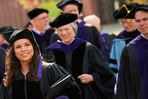 Graduates in black robes with purple accents walking.