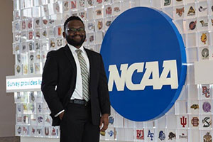 An African American man stands in front of an NCAA logo. Tiles featuring logos of various teams decorate the wall behind him.
