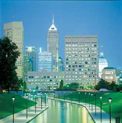 A rendering of Indianapolis at dusk. Thin, black lampposts line a canal that runs toward gray skyscrapers.