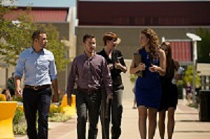 Students in button-down shirts or dresses walk down a path in groups, conversing.