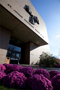 Angled view of the School of Law entryway. Purple shrubs line the path leading to the building.