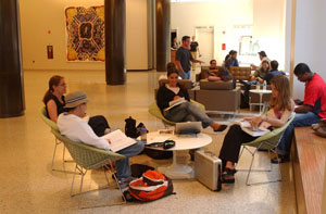 Students are seated in clusters at an open study area in a large hallway.