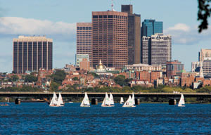 View of Boston. In the foreground, sailboats on the water. In the background, a cityscape with skyscrapers.