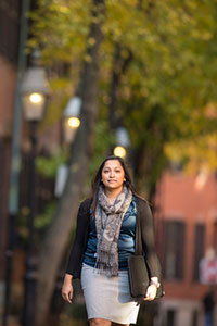 Female student walking, with a briefcase bag slung over her shoulder. In the background are lit lampposts, deciduous trees, and brick buildings with black shutters.