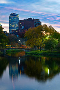 Boston at dusk. Pink and blue stratus clouds spread across the sky. In the foreground, trees and a skyscraper are reflected on a river. A footbridge stretches over a narrow portion of the river.