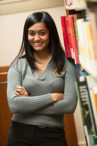 A female student leans against a shelf of library books, smiling.