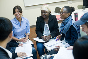 Inside a classroom, diverse students sit in a circle, listening and smiling, as one student speaks. Each student holds a pen and a pile of papers.