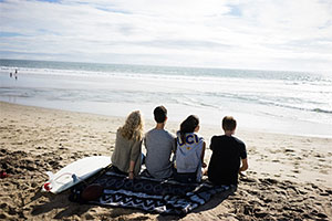 Four students sit on a blanket at the beach.
