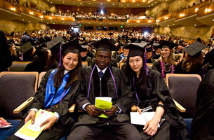 Three diverse graduates pose together, seated, in a bright room crowded with other graduates and guests.