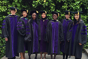 Diverse graduates, wearing black robes with purple accents, pose on a stairway platform outdoors.