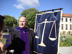 A male graduate wearing a black robe with purple accents holds a blue flag depicting scales.