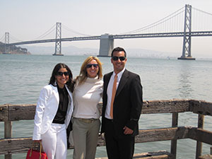 Three students--two female, one male--pose on a  wooden dock, in view of a long, gray bridge.