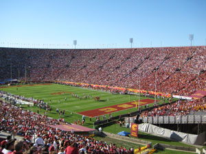 The USC stadium is packed with fans wearing red or white shirts.