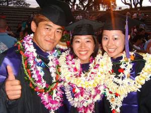 Three graduates wearing leis—1 male, 2 female—pose after the ceremony, smiling. One graduate is giving a 'thumbs up.'