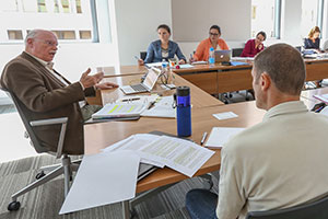 A professor speaks to his students. He is seated with the students at a U-shaped configuration of tables.