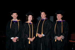 Four graduates, wearing their caps and gowns, pose for a photo.