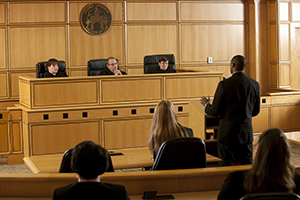 A man speaks in front of a bench of judges in a mock courtroom.