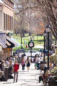 Students walk down a sidewalk lined on both sides with occupied cafe tables. There is a Starbucks, pub, and a restaurant to their right. An ornate clock stands at the end of the sidewalk, behind the students. Behind the clock, people are seated or playing frisbee in a grassy park.