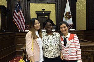 Three diverse, female students pose, smiling, in a courtroom.