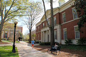 Angled view of School of Law--a red brick building with white accents. A student, talking on her cell phone, sits on a black bench in front of the school. Other students walk along a path that is lined with budding trees and black lampposts.