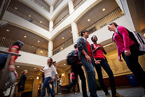 Angled, upward view of diverse students chatting in an atrium.