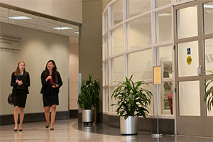 Two women walk down a curved hallway. Potted plants are to their left, outside of a room with glass walls.