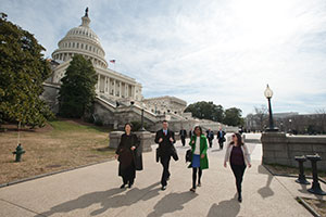 People walk down a sidewalk in front of the United States Capitol.