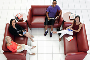 An overhead view of four students sitting on red loveseats. Two hold tablets; one, a book; the other, paper. The floor is tiled white.