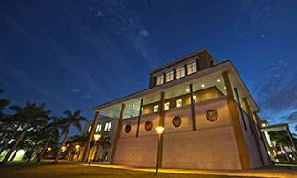 Angled view of a university building at night. Palm trees stand next to the building. A row of lit lampposts line the front of the building.