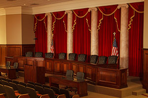 A moot courtoom. Five red curtains, trimmed in gold, hang behind the bench. Two American flags also stand behind the bench.