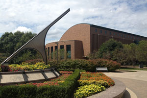 A modern sculpture, surrounded by flowers, points toward the cloudy sky. In the background, the law school building is made of brick and has a mixture of curved and angled edges. Many deciduous trees are in view.