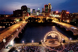 Des Moines at night. The city is brightly lit. An event is happening on an outdoor stage along the water. Many people are in attendance.