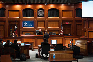 A student stands before the bench during a mock trial. A blue sign, embedded into the wall behind the bench, says, 'St Mary's University School of Law.' An American flag and two other flags also stand behind the bench