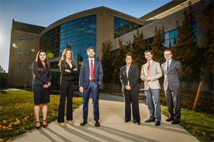 Six people wearing suits pose in front of the law school.