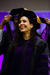 A female graduate smiles during the commencement.