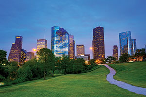 Houston at night. A winding footpath cuts through a grassy field, toward a backdrop of skyscrapers. A patch of deciduous trees stand to the left of the path.