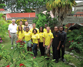 A group of people pose outdoors. Several of them are wearing yellow T-shirts.