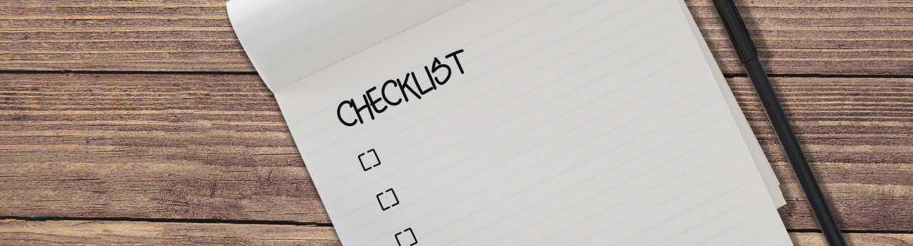 Checklist on pad with pen on wooden table