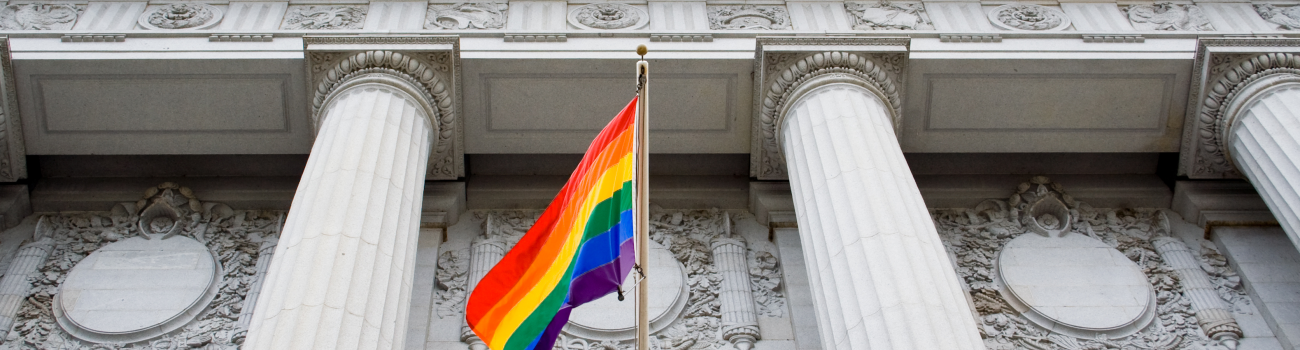 Rainbow flag in front of building with columns.