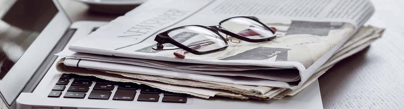 Reading glasses lying on top of newspaper and laptop.