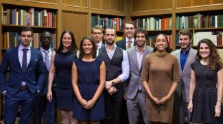 Group of law students in front of law library bookshelves.
